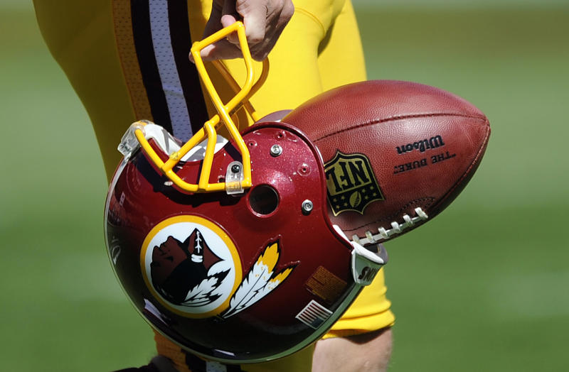 """In this Sept. 23, 2012, file photo, Washington Redskins punter Sav Rocca carries a football in his helmet before an NFL football game against the Cincinnati Bengals in Landover, Md. The U.S. Patent Office ruled Wednesday, June 18, 2014, that the Washington Redskins nickname is """"disparaging of Native Americans"""" and that the team's federal trademarks for the name must be canceled. The ruling comes after a campaign to change the name has gained momentum over the past year"""