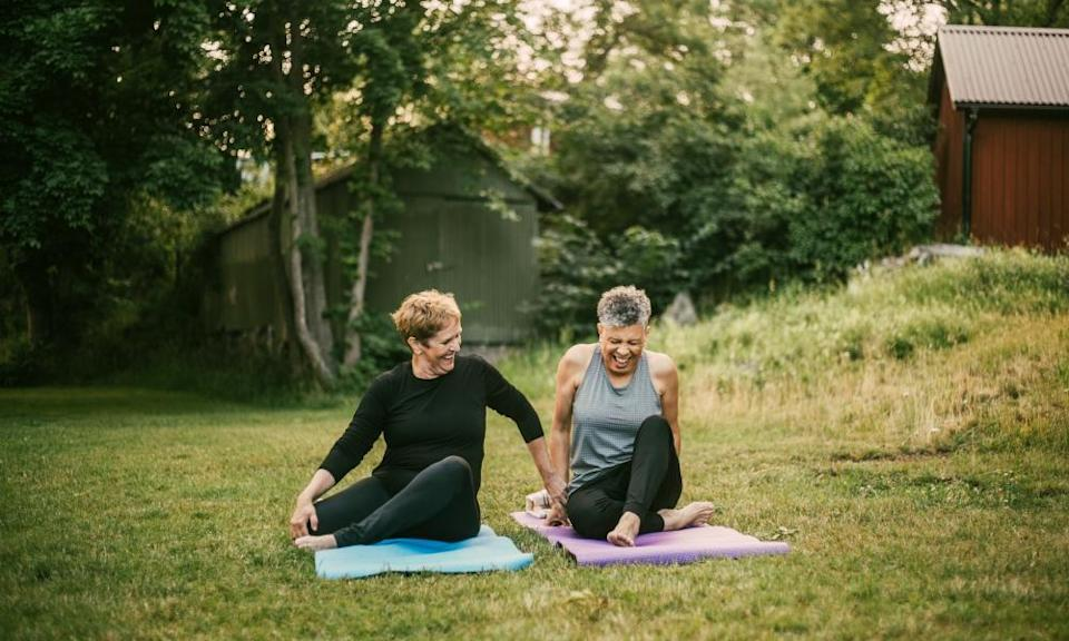 Smiling woman assisting friend while exercising on mat in public park