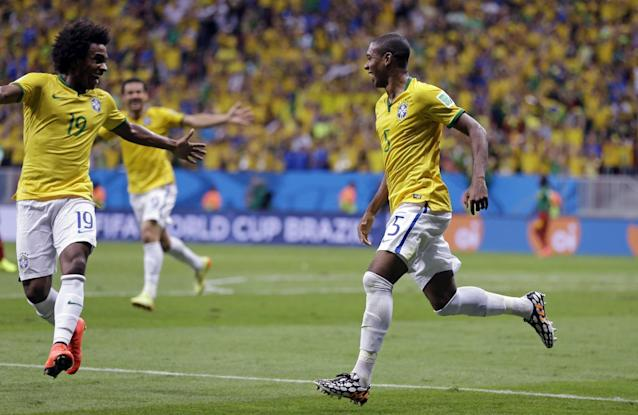 Brazil's Fernandinho, right, celebrates scoring his side's fourth goal during the group A World Cup soccer match between Cameroon and Brazil at the Estadio Nacional in Brasilia, Brazil, Monday, June 23, 2014. (AP Photo/Andre Penner)