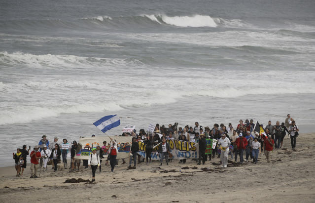 <p>Demonstrators march to meet Central American migrants traveling in a caravan for a gathering at the border on the beach where the border wall ends in the ocean, April 29, 2018, in San Diego. (Photo: Chris Carlson/AP) </p>