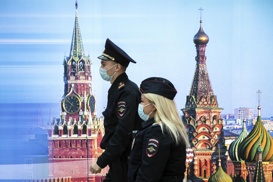 Police officers wearing face masks to protect against coronavirus walk past a photo of Kremlin's Spasskaya Tower, left, and St. Basil's Cathedral in Sheremetyevo Airport, outside Moscow, Russia, Friday, Oct. 9, 2020. The coronavirus outbreak in Russia continues its rapid growth. (AP Photo/Pavel Golovkin)