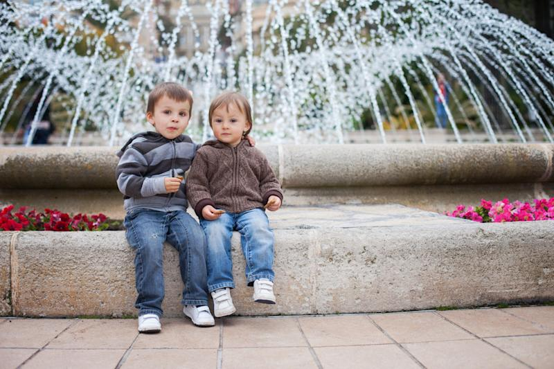 Two boys sitting in front of a fountain. Image: Getty