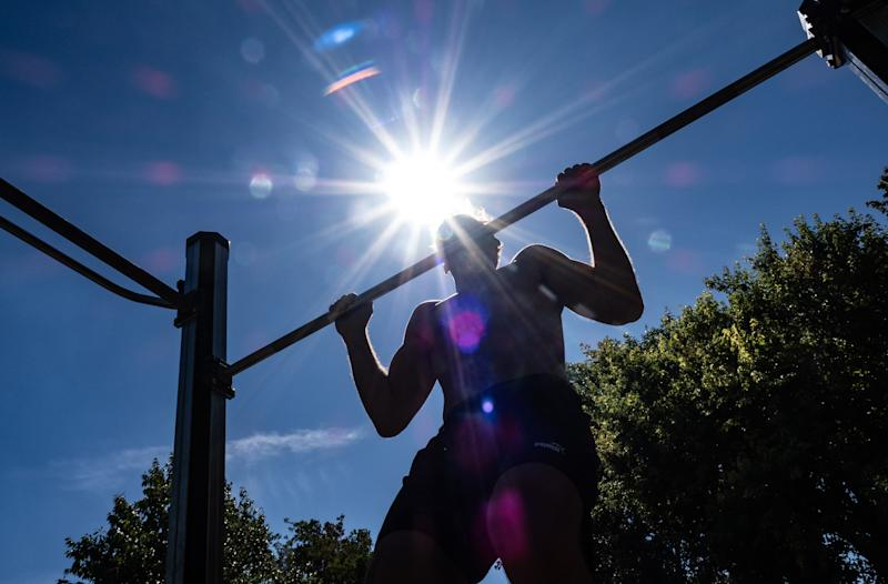 21 August 2020, Berlin: Lukas (25) trains at high temperatures in the Volkspark Friedrichshain on a pole of an outdoor device. Photo: Paul Zinken/dpa-Zentralbild/dpa (Photo by Paul Zinken/picture alliance via Getty Images)