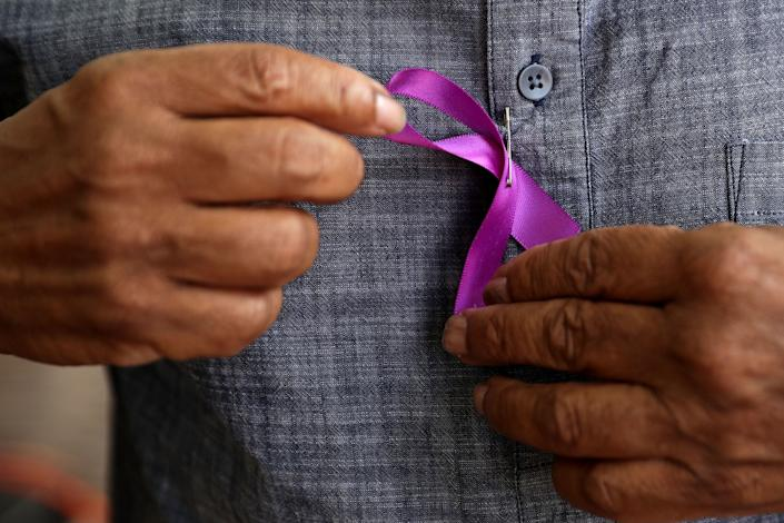 A man puts on a purple ribbon while waiting in line.