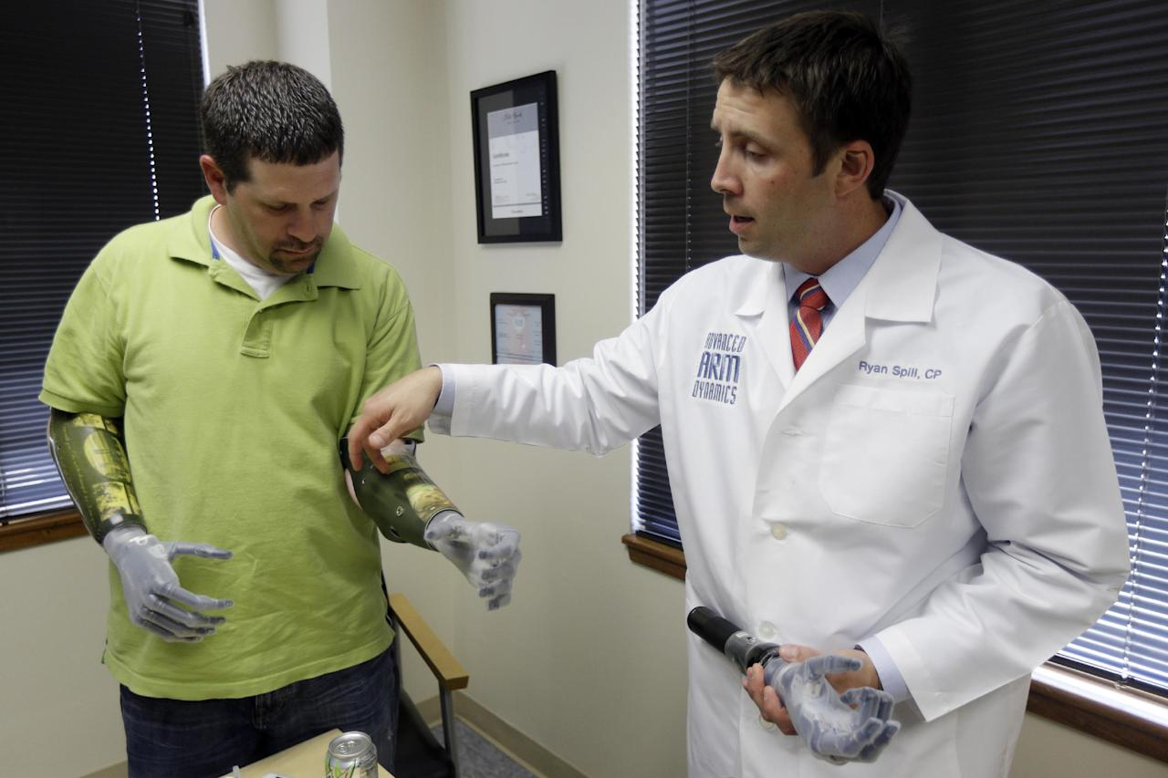 Double amputee Jason Koger, 34, of Owensboro, Ky., accompanied by prosthetist for Advanced Arm Dynamics, Ryan Spill, demonstrates his i-limb ultra revolution prosthetic hands during an interview with the Associated Press, Thursday, May 2, 2013, in Philadelphia. Koger, a husband and father of three who lost his limbs in an accident, can now activate with an iPhone app 24 different grip patterns for his new hands. (AP Photo/Matt Rourke)