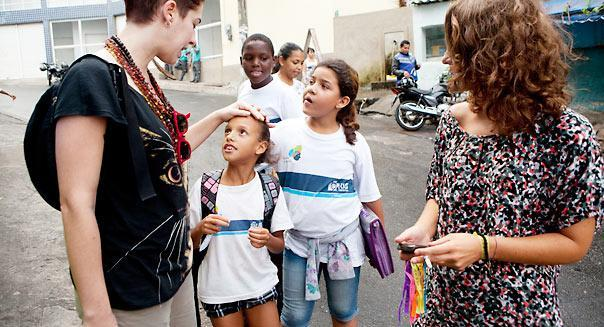 """<b class=""""credit"""">Melanie Stetson Freeman/The Christian Science Monitor via Getty Images</b>Tatiana Coelho (l.) and Rute Honrado chat with children in Rio de Janeiro, Brazil. Mothers in Brazil have been found to talk most often to their children about finances."""