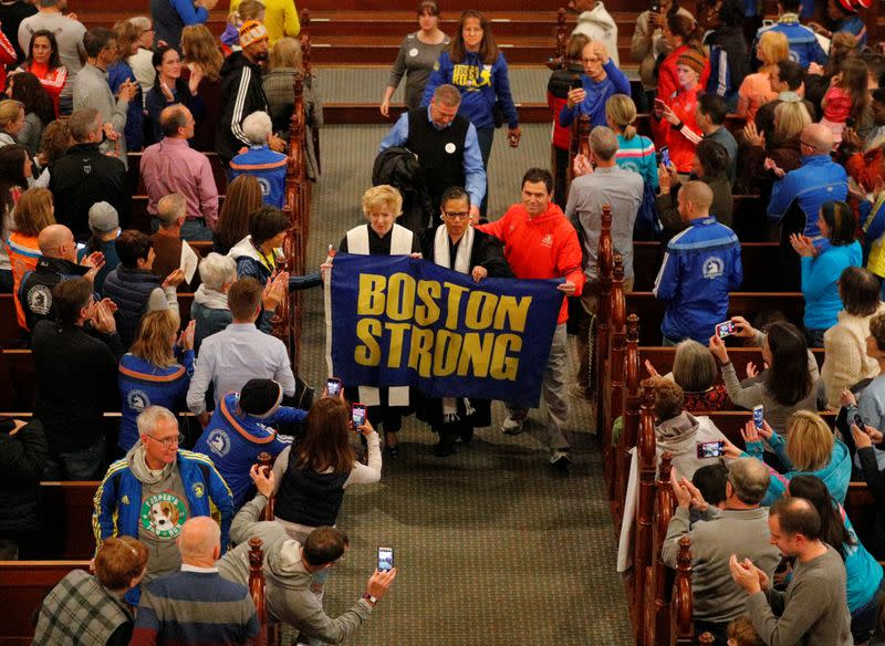 Boston Marathon bombing witness Carlos Arredondo blesses the runners during a service at Old South Church in Boston