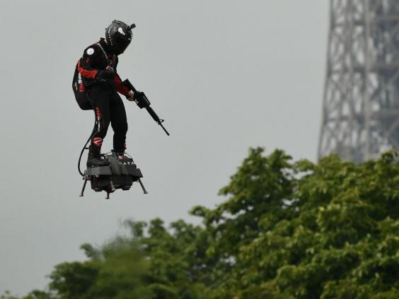 Zapata CEO Franky Zapata flies a jet-powered hoverboard or 'Flyboard prior to the Bastille Day military parade down the Champs-Elysees avenue in Paris on 14 July, 2019 (AFP/Getty Images)