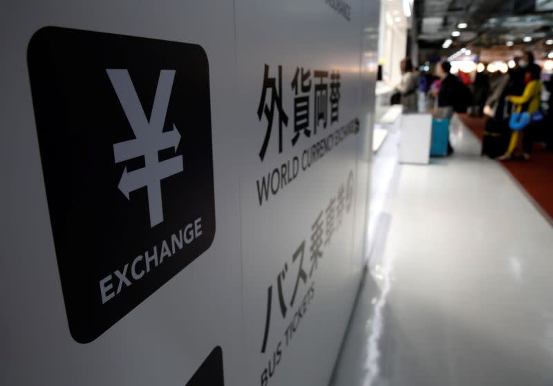 FILE PHOTO: A Japanese yen currency sign is seen at a currency exchange office as people line up to exchange money at Narita International airport