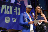 Boston Red Sox outfielder Mookie Betts stands with MLS host Susannah Collins as he announces the selection of Jalil Anibaba as the team's third pick during the Major League Soccer expansion draft Tuesday, Nov. 19, 2019, in Nashville, Tenn. (AP Photo/Mark Zaleski)