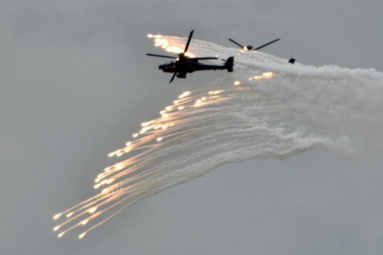 Two US-made Apache attack helicopters release flares during annual military drills in Taichung, Taiwan, in July 2020