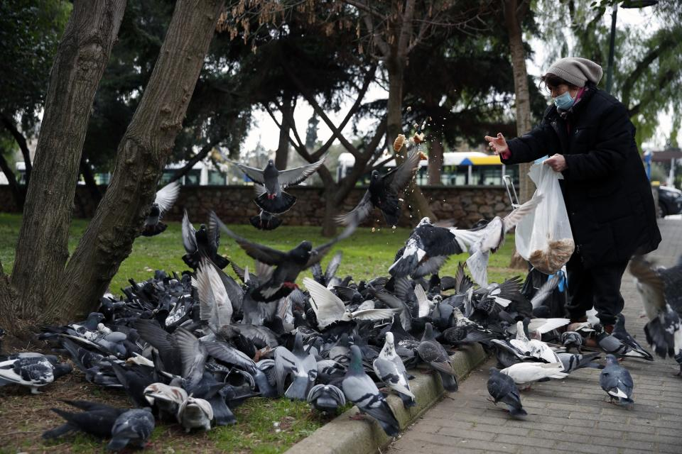 A woman wearing a face mask to prevent the spread of coronavirus, feeds pigeons at a park in Athens, Friday, Jan. 22, 2021. Greece's government has extended nationwide lockdown measures indefinitely as a nightly curfew, domestic travel restrictions and stay-at-home orders will all remain in effect after being first imposed in early November. (AP Photo/Thanassis Stavrakis)