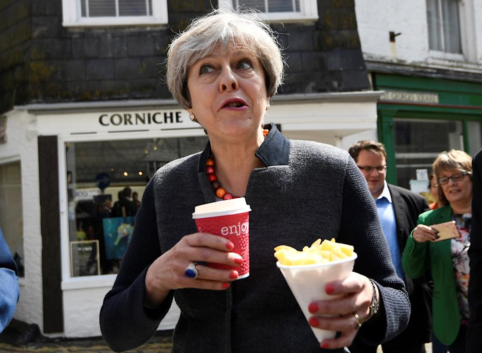 Prime Minister Theresa May having some chips while on a walkabout during an election campaign stop in Mevagissey, Cornwall. Unfortunately it is not known if she finished the chips as both her hands appear to be full. Photo dated 02/05/17 (PA)