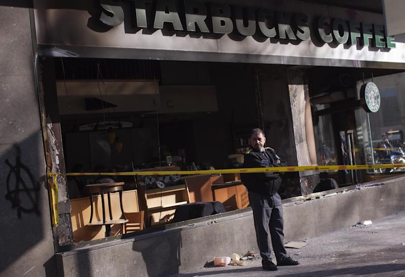 A security guard stands next to a Starbucks coffee shop stormed by demonstrators during clashes between police and protesters after a general strike in Barcelona, Spain, Friday, March 30, 2012. The Spanish government prepared to approve on Friday a new austerity budget that hundreds of thousands protested against this week in sometimes violent demonstrations. (AP Photo/Emilio Morenatti)