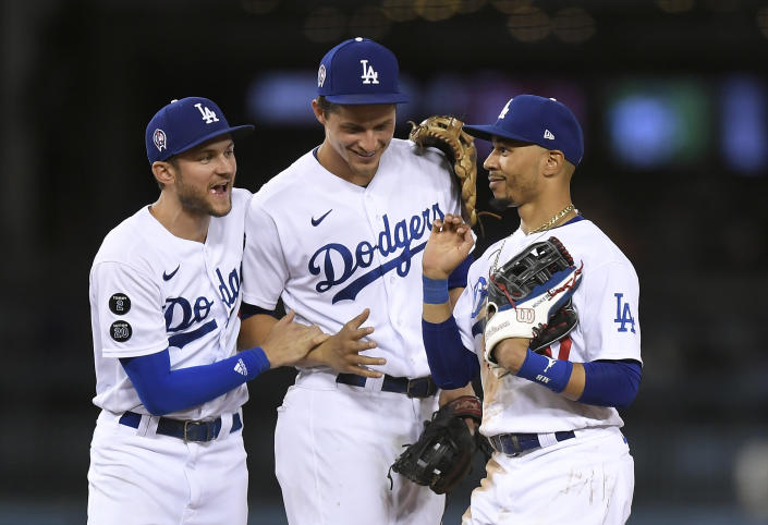 LOS ANGELES, CA - SEPTEMBER 11: Mookie Betts #50 of the Los Angeles Dodgers celebrate with Trea Turner #6 and Corey Seager #5 after defeating the San Diego Padres 5-4 at Dodger Stadium on September 11, 2021 in Los Angeles, California. (Photo by Kevork Djansezian/Getty Images)