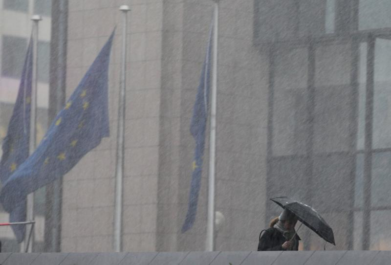 A woman walks through heavy snow and rain showers in front of the European Council building in Brussels, Thursday, Feb. 7, 2013. European Union leaders braced for all-night negotiations in Brussels to try and strike a deal on EU spending for the next seven years, especially after the summit start was delayed by hours. (AP Photo/Yves Logghe)