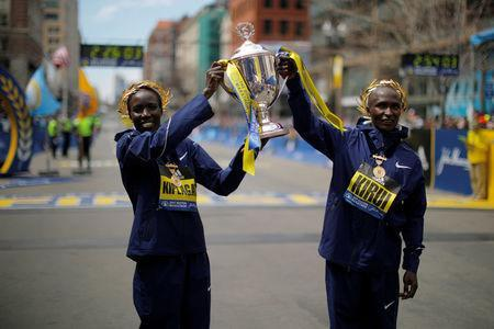 Women's division winner Edna Kiplagat (L) and men's division winner Geoffrey Kirui, both of Kenya, pose with the trophy at the finish line of the 121st Boston Marathon in Boston, Massachusetts. REUTERS/Brian Snyder