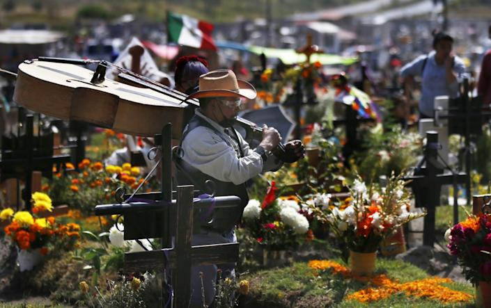 A musician carries a large upright bass over his shoulder while walking between flower-covered gravesites