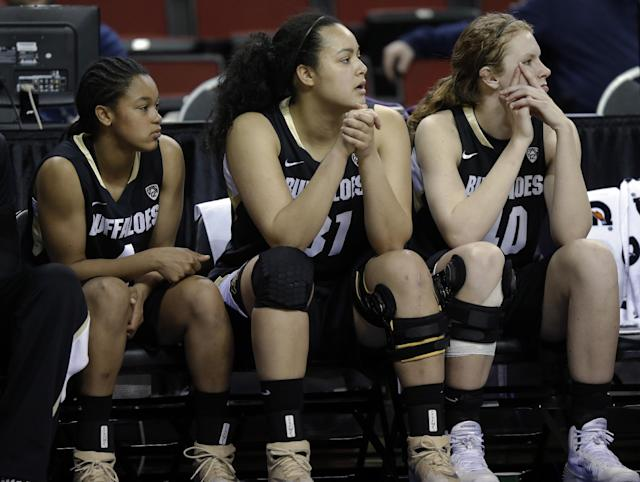 Colorado's Desiree Harris, left, Zoe Beard-Fails, center, and Rachel Hargis, right, watch from the bench in the second half of an NCAA college basketball game against Stanford in the second round of the Pac-12 women's tournament, Friday, March 7, 2014, in Seattle. Stanford won 69-54. (AP Photo/Ted S. Warren)