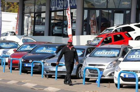 A man walks past a car dealership with car prices displayed in Johannesburg