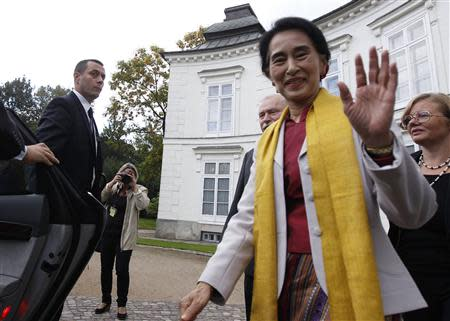 Myanmar's opposition leader Aung San Suu Kyi waves after her meeting with former Polish president Lech Walesa (3rd R) in Myslewicki Palace in Warsaw September 12, 2013. REUTERS/Kacper Pempel