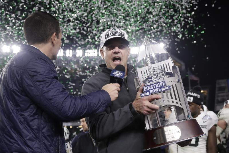 Michigan State head coach Mark Dantonio, right, speaks while holding the Pinstripe Bowl NCAAcollege football game trophy after playing Wake Forest, Friday, Dec. 27, 2019, in New York. (AP Photo/Frank Franklin II)