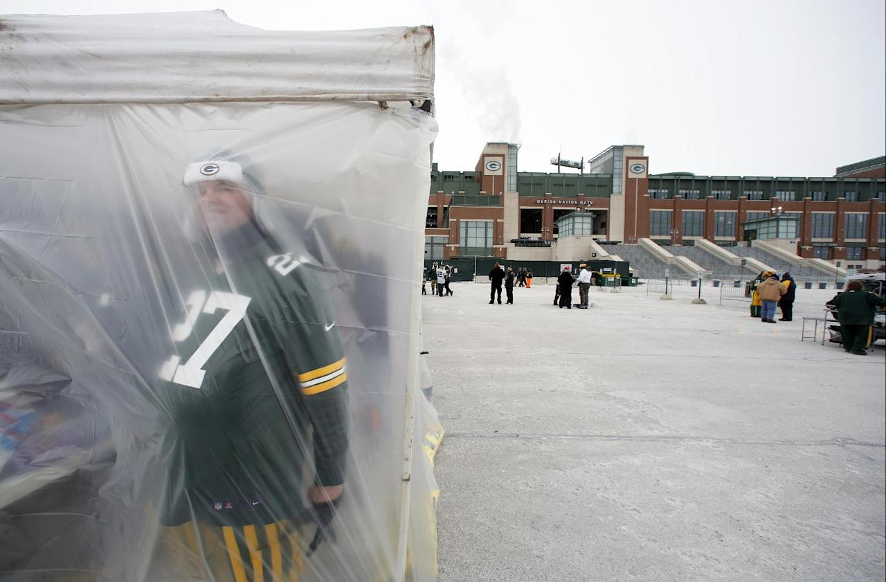 A Green Bay Packers fan looks through a tent as fans tailgate before an NFL wild-card playoff football game between the Green Bay Packers and the San Francisco 49ers, Sunday, Jan. 5, 2014, in Green Bay, Wis. (AP Photo/Jeffrey Phelps)