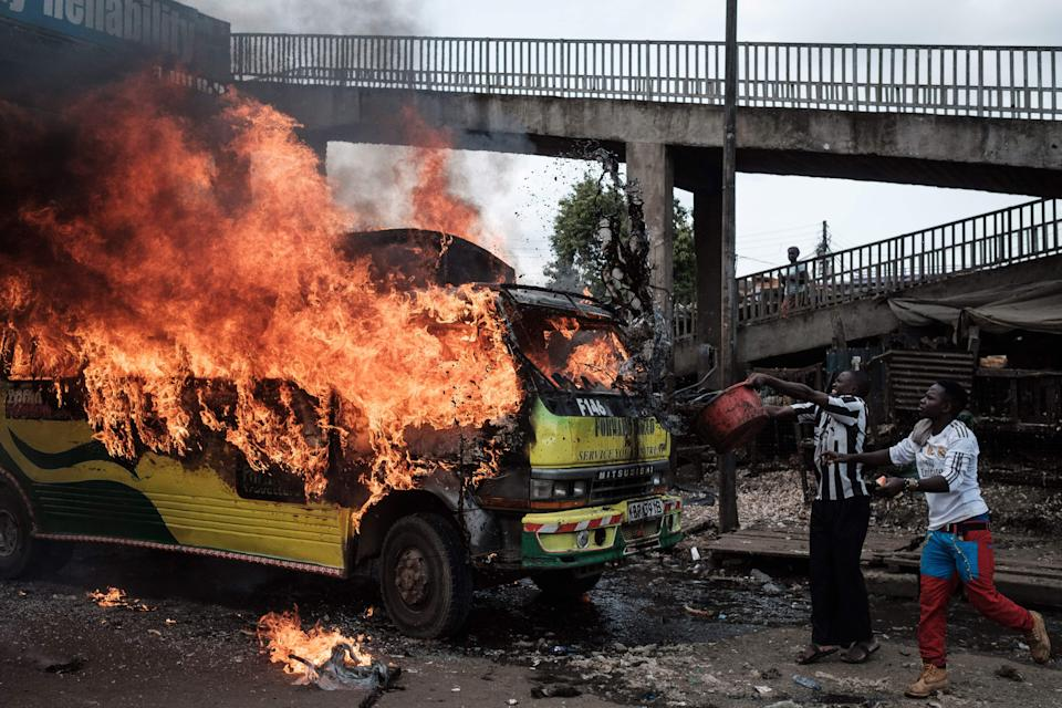 <p>Supporters of Kenyan's opposition party National Super Alliance (NASA) throw water onto a burning bus during a demonstration on Nov. 17, 2017 in Nairobi. (Photo: Yasuyoshi Chiba/AFP/Getty Images) </p>