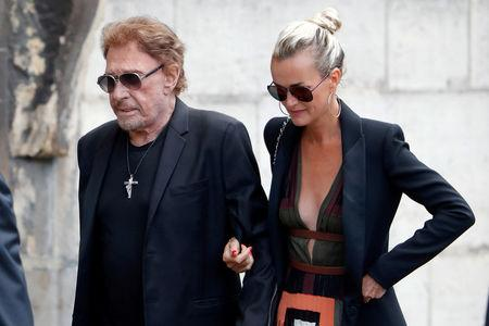 FILE PHOTO: French singer and actor Johnny Hallyday (L) and his wife Laeticia attend the funeral ceremony of late actress Mireille Darc at the Saint-Sulpice church in Paris, France, September 1, 2017. REUTERS/Charles Platiau/File Photo