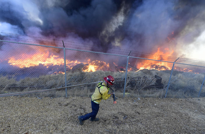 A firefighter pulls a water line as he begins to battle a mulch and pallet fire burning out of control, fanned by Santa Ana winds in and around a recycling yard near Wilson Street and Fleetwood Drive in Riverside, Calif., Thursday, Dec. 3, 2020. Firefighters from both Riverside and San Bernardino County, along with assistance from Colton, Rialto and Riverside City Fire fought the blaze. (Will Lester/The Orange County Register via AP)
