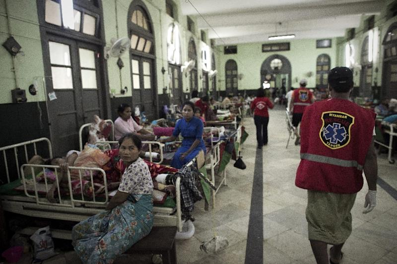 Noble Heart rescue ambulance charity service volunteers walk into a ward to transfer a patient at the Yangon general hospital (AFP Photo/Nicolas Asfouri)