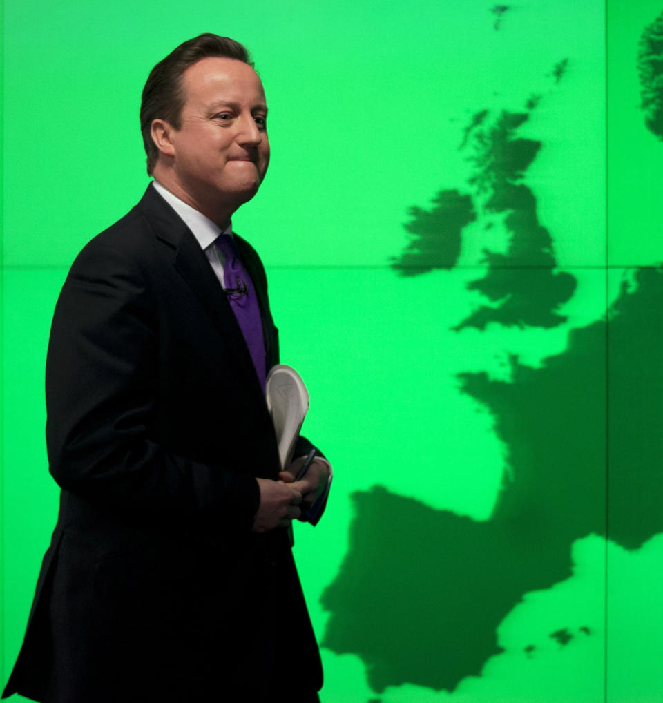 FILE - In this Wednesday, Jan. 23, 2013 file photo, Britain's Prime Minister David Cameron walks past a map of Europe on a screen after making a speech on holding a referendum on staying in the European Union in London. Britain and the European Union have struck a provisional free-trade agreement that should avert New Year's chaos for cross-border commerce and bring a measure of certainty to businesses after years of Brexit turmoil. The breakthrough on Thursday, Dec. 24, 2020 came after months of tense and often testy negotiations that whittled differences down to three key issues: fair-competition rules, mechanisms for resolving future disputes and fishing rights. (AP Photo/Matt Dunham, File)