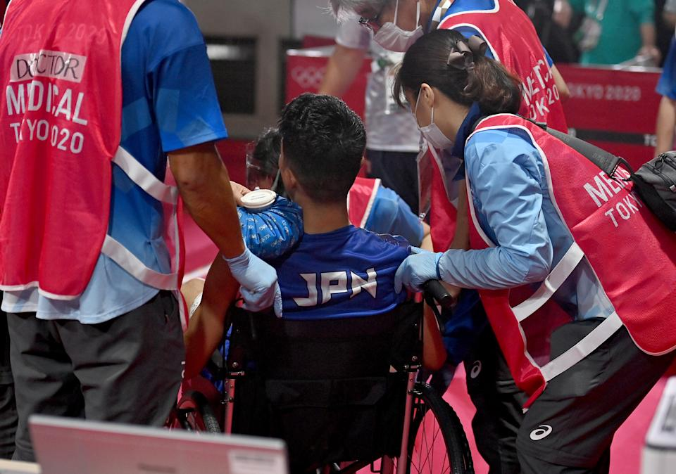 TOKYO, JAPAN - AUGUST 03: Ryomei Tanaka of Team Japan gets medical treatment during the Men's Fly (48-52kg) quarter final on day eleven of the Tokyo 2020 Olympic Games at Kokugikan Arena on August 03, 2021 in Tokyo, Japan. (Photo by Luis Robayo - Pool/Getty Images)