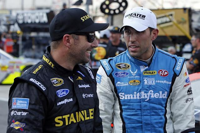 FILE - In this Aug. 23, 2013 file photo, Aric Almirola, right, talks with Marcos Ambrose during qualifying for the NASCAR Irwin Tools Night Race in Bristol, Tenn. In 75 races as teammates, Almirola and Ambrose had never before run in the top-five together. They finally broke through at Bristol Motor Speedway, where Richard Petty Motorsports scored its best overall day as an organization in years. (AP Photo/Wade Payne, File)