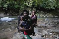 A migrant carries two children across a river as they continue their trek north, near Acandi, Colombia, Wednesday, Sept. 15, 2021. The migrants, mostly Haitians, are on their way to crossing the Darien Gap from Colombia into Panama dreaming of reaching the U.S. (AP Photo/Fernando Vergara)