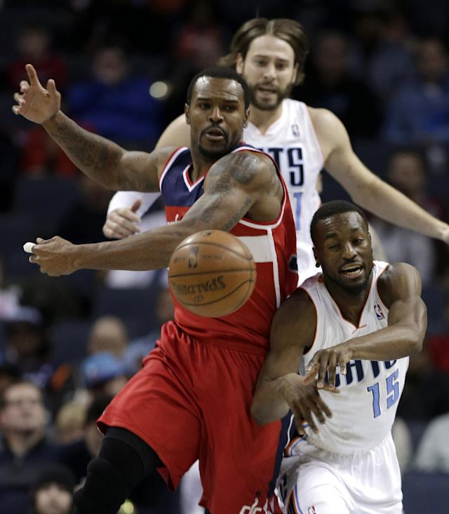 Charlotte Bobcats' Kemba Walker, right, and Washington Wizards' Trevor Booker, left, chase a loose ball as Charlotte's Josh McRoberts, back, looks on watches during the first half of an NBA basketball game in Charlotte, N.C., Tuesday, Jan. 7, 2014. (AP Photo/Chuck Burton)