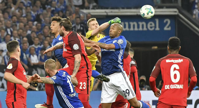 Frankfurt goalkeeper Lukas Hradecky and Schalke's Naldo challenge for the ball during the German soccer cup semifinal match between FC Schalke 04 and Eintracht Frankfurt in Gelsenkirchen, Germany, Wednesday, April 18, 2018. (AP Photo/Martin Meissner)