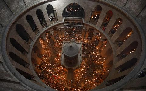 Christian Orthodox worshippers hold up candles during the ceremony of the