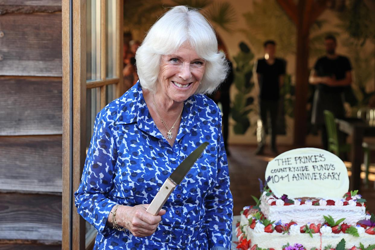 The Duchess of Cornwall prepares to cut a cake to mark the