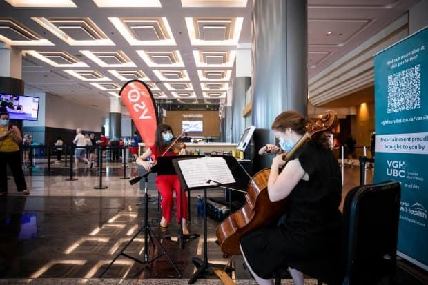 Members of the Vancouver Symphony Orchestra perform for people at the COVID-19 vaccination clinic at the Vancouver Convention Centre on June 24.  (Ben Nelms/CBC - image credit)