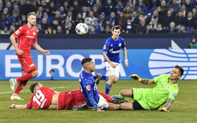 Union's Florian Hubner, Schalke's Amine Harit and Union's goalkeeper Rafal Gikiewicz, from left, challenge for the ball during the German Bundesliga soccer match between FC Schalke 04 and Union Berlin in Gelsenkirchen, Germany, Friday, Nov. 29, 2019. (AP Photo/Martin Meissner)