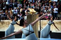 Priestesses dance around the Olympic flame during the handover ceremony at the Panathinean stadium in Athens, on April 27, 2016 (AFP Photo/Aris Messinis)