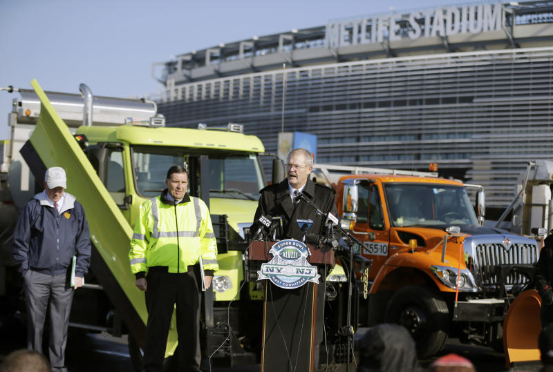 Alfred F. Kelly, Jr., left, President and CEO of the NY/NJ Super Bowl Host committee, and NJ department of transportation deputy commissioner Joseph Mrozek, center, stand near large snow plows as they listen to President and CEO of MetLife stadium, Brad Mayne, answer a question at MetLife stadium in East Rutherford, N.J., Wednesday, Dec. 18, 2013, as officials demonstrated snow removal and melting machinery and outlined emergency weather scenarios and contingency plans for the Super Bowl in February. (AP Photo/Mel Evans)