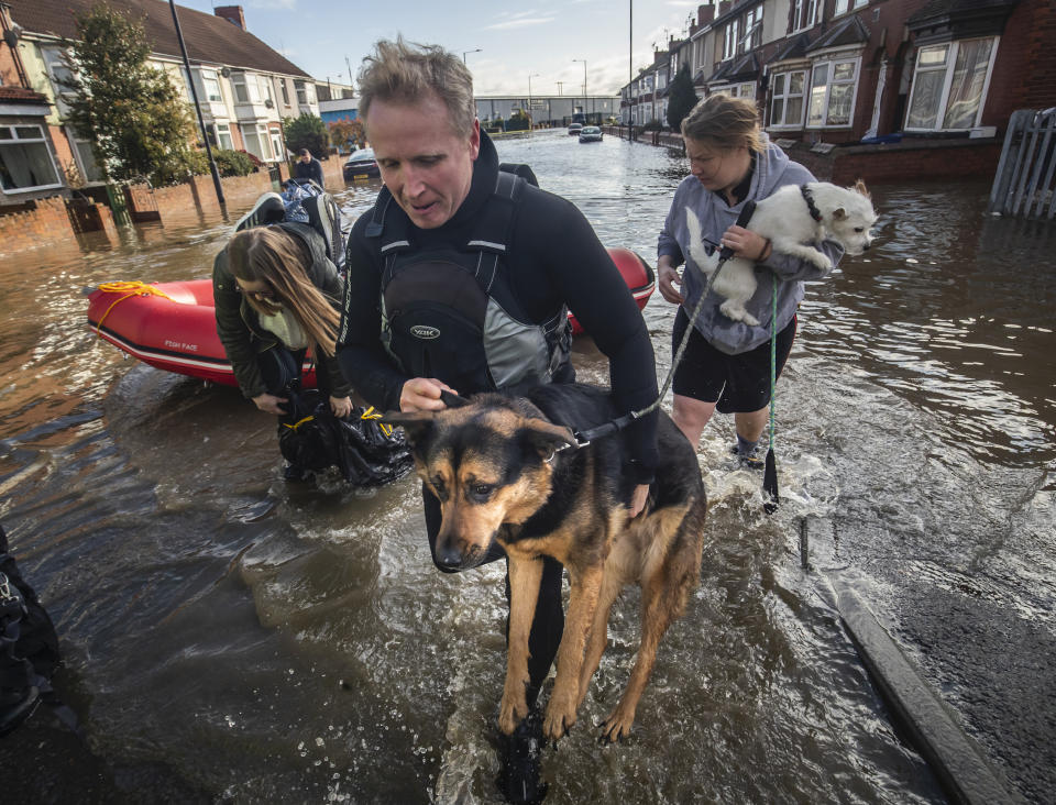 A dog is carried to safety on Yarborough Terrace in Doncaster, Yorkshire, as parts of England endured a month's worth of rain in 24 hours, with scores of people rescued or forced to evacuate their homes, others stranded overnight in a shopping centre, and travel plans thrown into chaos.