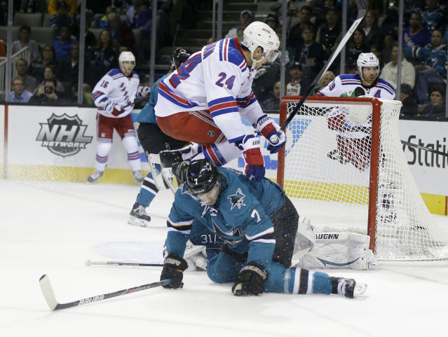 New York Rangers' Ryan Callahan (24) jumps over San Jose Sharks' Brad Stuart (7) during the second period of an NHL hockey game on Tuesday, Oct. 8, 2013, in San Jose, Calif. (AP Photo/Marcio Jose Sanchez)