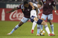 Colorado Rapids midfielder Kellyn Acosta, left, struggles with Vancouver Whitecaps midfielder Ryan Gould in the first half of an MLS soccer match Sunday, Sept. 19, 2021, in Commerce City, Colo. (AP Photo/David Zalubowski)