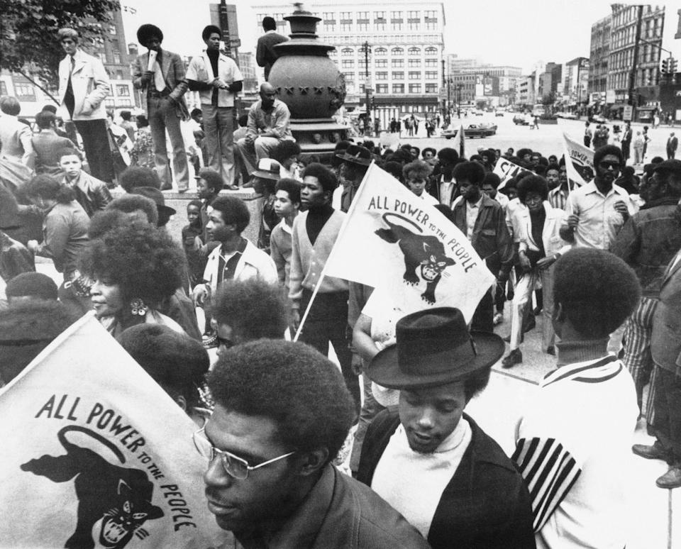 RIGHT: A crowd of 4,000 to 5,000 people, some carrying Black Panther flags, staged a protest march and rally in downtown Detroit against the police STRESS unit, Thursday, Sept. 24, 1971.
