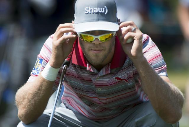 Graham DeLaet checks his line while on the second green during the third round of play at the Canadian Open golf championship in Montreal on Saturday, July 26, 2014. (AP Photo/The Canadian Press, Paul Chiasson)