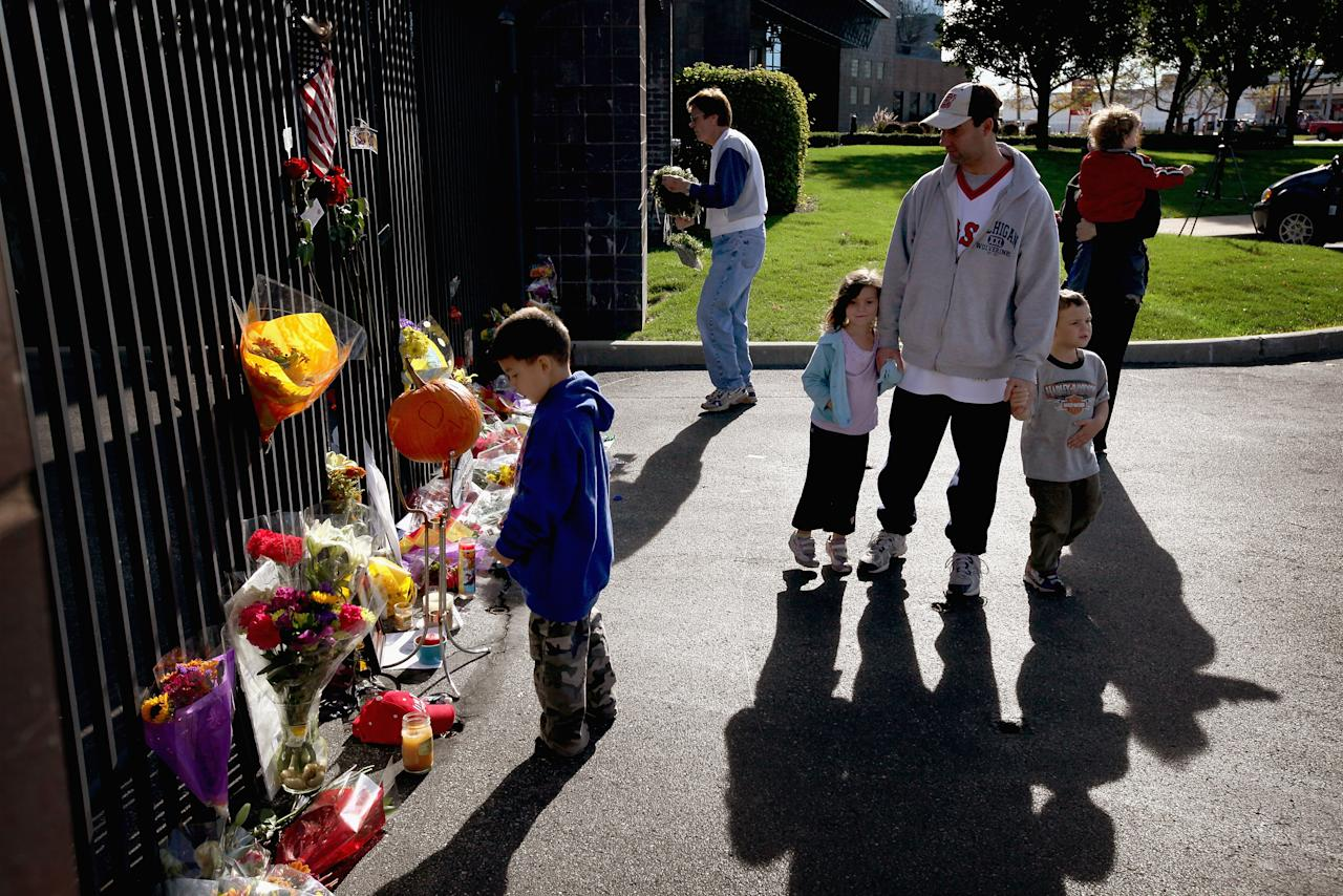 INDIANAPOLIS, IN - OCTOBER 17:  Fans look over tributes to two-time Indianapolis 500 winner Dan Wheldon which have been left at a memorial at the gate of the Indianapolis Motor Speedway on October 17, 2011 in Indianapolis, Indiana. Wheldon, winner of the 2011 Indy 500, was killed in a crash yesterday at the Izod IndyCar series season finale at Las Vegas Motor Speedway.  (Photo by Scott Olson/Getty Images)