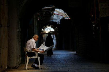 A man sits in an alley in the Christian Quarter of Jerusalem's Old City June 21, 2016. REUTERS/Ronen Zvulun